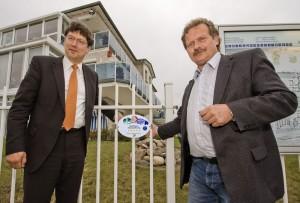 Der Präsident des Deutschen Tourismus Verbandes Reinhard Meyer und der Geschäftsführer der Touristik-Service-Kühlungsborn GmbH, Peter Brauer, bringen das 5-Sterne-Schild an der Strandresidenz-Kühlungsborn an.